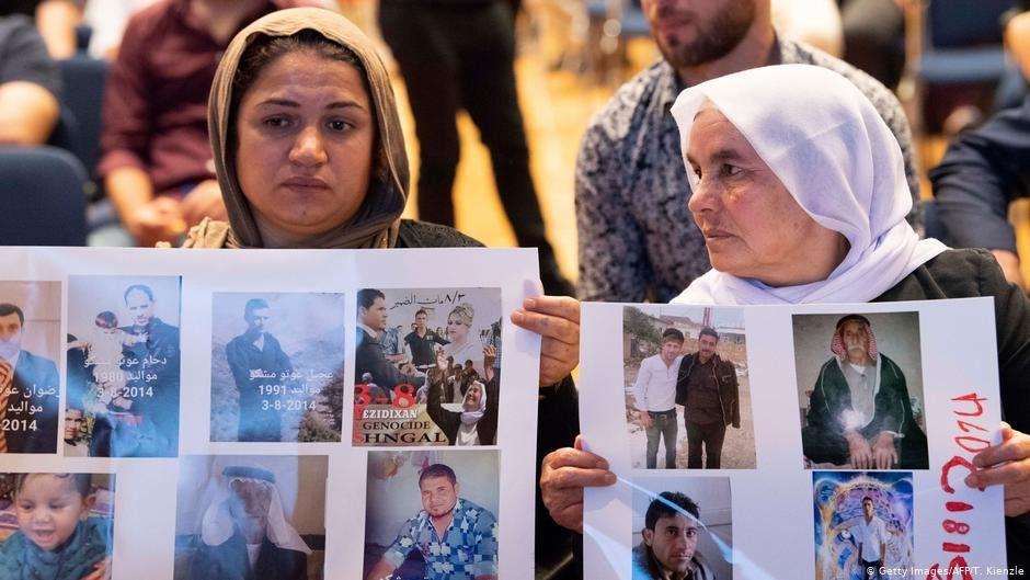 ايزيديتان تحملان صور مغيبين على يد داعش من افراد عائلاتهما