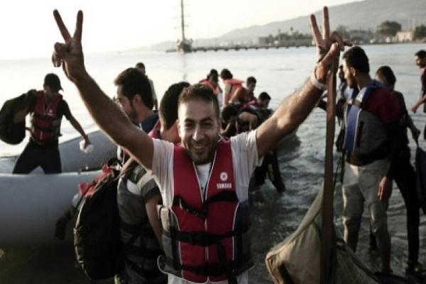 لاجئ يعرب عن فرحته بسلامة الوصول الى جزيرة يونانية بعد عبور بحر ايجه